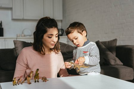woman and little son playing toy dinosaurs at table in living room at home