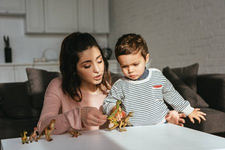 focused woman and little boy playing toy dinosaurs at table in living room at home