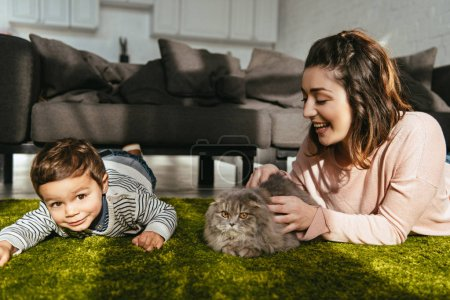 adorable boy and his mother playing with british longhair cat on floor at home