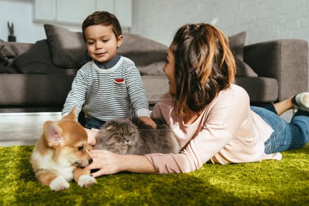 mother and son laying on floor with dog and cat in living room at home