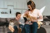 """Постер, картина, фотообои """"улыбаясь, мать и сын, сидя на диване с кошка и собака в гостиной дома"""""""