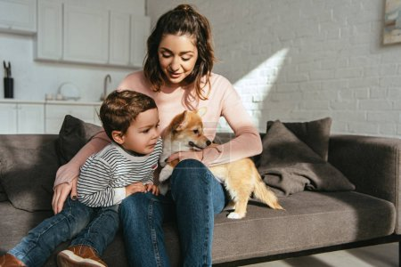 selective focus of woman and her little son sitting on sofa with adorable corgi at home