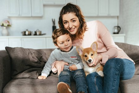 happy mother and her little son sitting on sofa with puppy at home