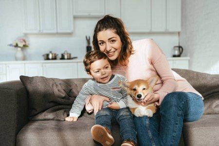 Foto de Madre y su pequeño hijo sentado en el sofá con cachorro de corgi en casa - Imagen libre de derechos