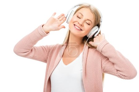 woman enjoying music, using headphones and smiling with closed eyes isolated on white