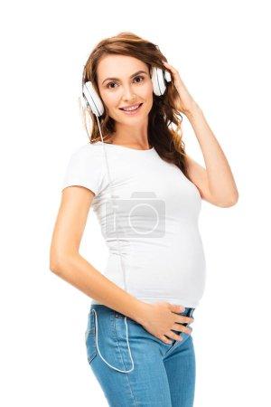Photo pour Femme enceinte écoute la musique et la tenue des écouteurs avec la main gauche isolé sur blanc - image libre de droit