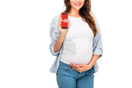 cropped view of beautiful pregnant woman holding smartphone with youtube app isolated on white