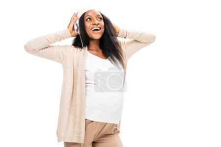 ecstatic african american pregnant woman listening music in headphones isolated on white