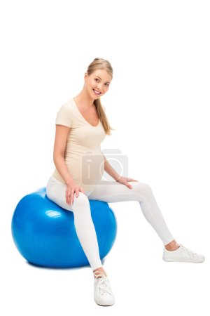 pregnant blonde woman sitting on fitness ball and holding hands on knees isolated on white