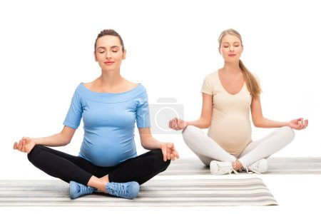 two pregnant women sitting on floor and meditating isolated on white