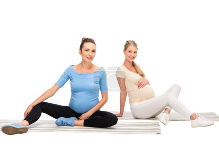 two pregnant women sitting on fitness mats isolated on white