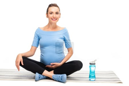 pregnant brown haired woman sitting in lotus pose with sport bottle isolated on white