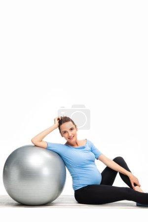 brown haired pregnant woman sitting on floor with fitness ball and looking to camera isolated on white