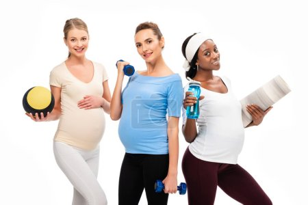 three smiling pregnant women holding dumbbells and fitness stuff isolated on white
