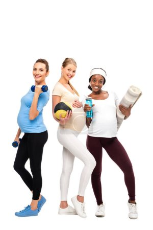 Photo for Three happy pregnant women standing with dumbbells and fitness equipment isolated on white - Royalty Free Image