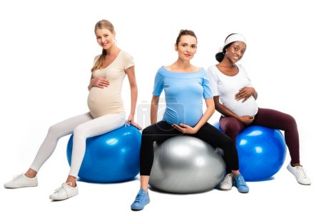 three happy pregnant women sitting on fitness balls isolated on white