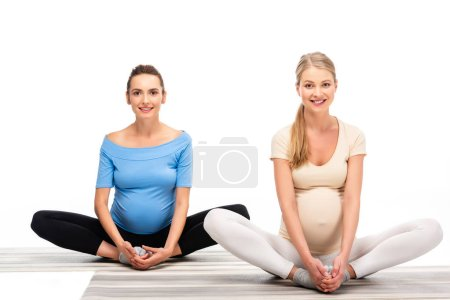 two pregnant women sitting on floor and holding hands on feet isolated on white