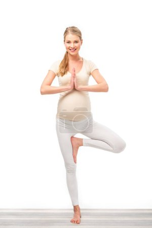 full length of pregnant blonde standing in tree pose isolated on white