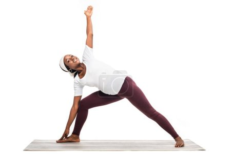 african american pregnant woman making yoga exercises on floor isolated on white