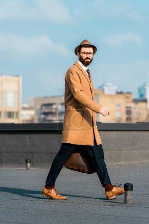 Foto de Hombre de negocios guapo caminando en el techo durante el día - Imagen libre de derechos