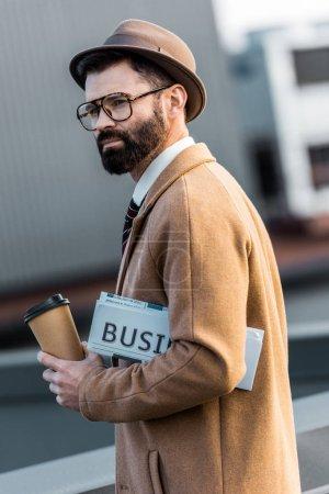 bel homme barbu avec café et journal d'affaires pour aller