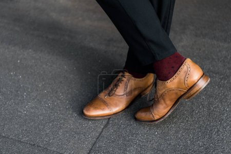 Photo for Cropped view of male crossed legs in burgundy socks and oxford shoes - Royalty Free Image