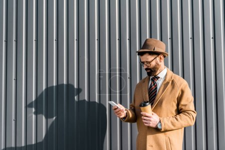businessman in coat and glasses using smartphone and holding coffee to go near wall with shadow