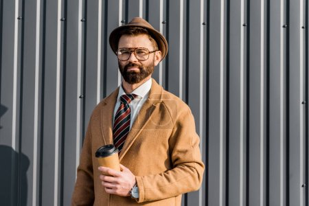 handsome bearded businessman holding coffee to go and looking at camera