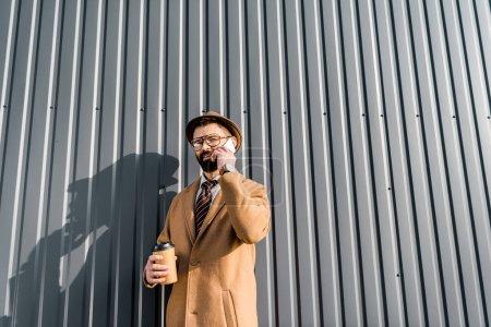 Photo pour Vue à angle bas de l'homme d'affaires parlant sur smartphone et tenant café à emporter - image libre de droit