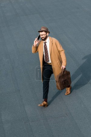 Photo for Handsome businessman with bag walking and talking on smartphone - Royalty Free Image