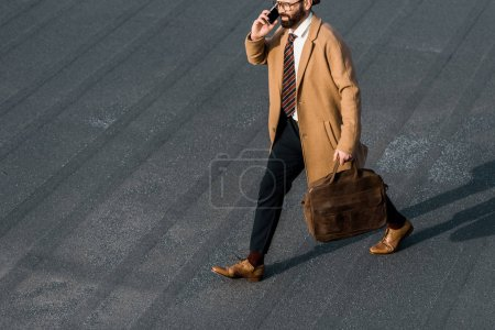 cropped view of bearded businessman in glasses talking on smartphone