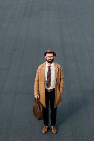 adult bearded businessman standing with leather bag and hand in pocket