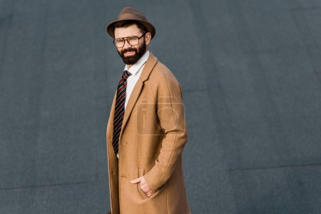 smiling bearded businessman in glasses posing with hand in pocket
