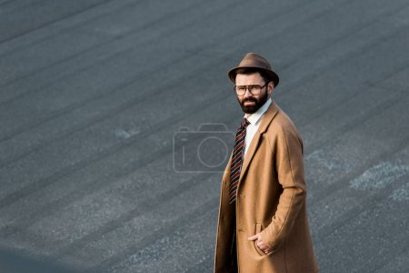 Photo for Confident businessman in glasses standing with hand in pocket and looking at camera - Royalty Free Image
