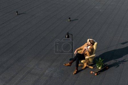hombre de negocios adulto descansando en sillón con cigarrillo en el techo