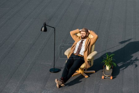 adult businessman in coat resting in armchair at daytime