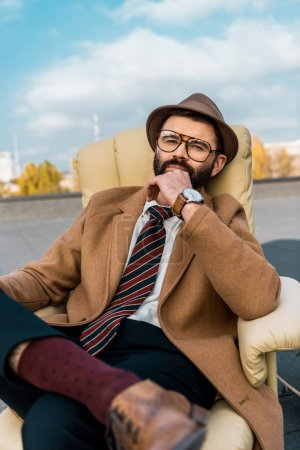 handsome bearded businessman sitting in armchair on roof