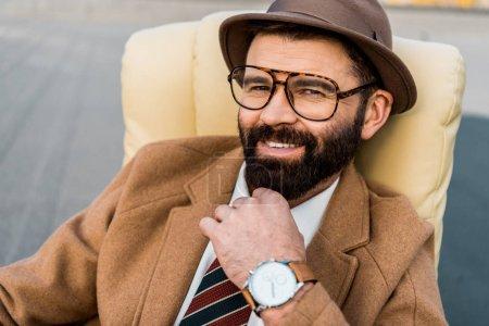 Photo pour Gros plan d'adulte homme d'affaires souriant en chapeau et des lunettes en regardant la caméra - image libre de droit
