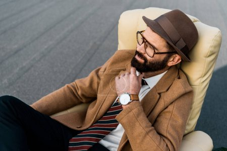 thoughtful bearded businessman in glasses sitting in armchair