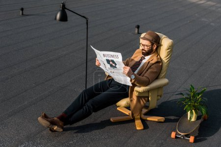 bearded man in coat reading business newspaper in armchair