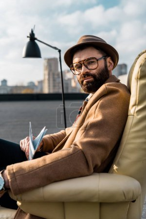 bearded businessman in glasses sitting in armchair with newspaper on roof