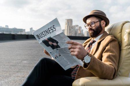 barbu de homme dans des verres de lecture de journal d'affaires en fauteuil sur toit