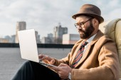 handsome businessman sitting in armchair and using laptop