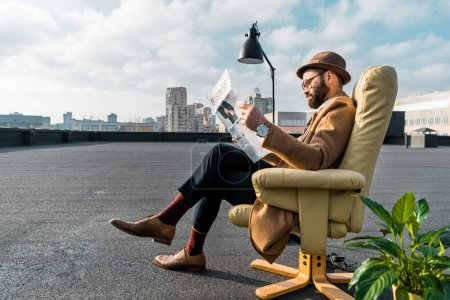 bearded businessman sitting in armchair and reading newspaper on roof