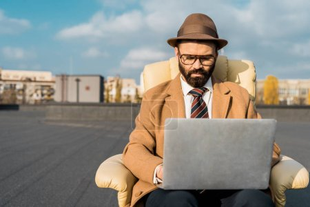 selective focus of businessman in armchair using laptop on roof