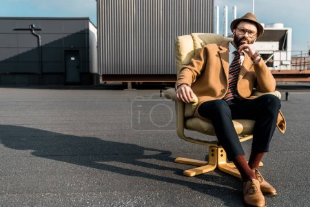 handsome adult businessman sitting in armchair on roof
