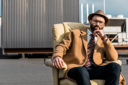adult businessman in hat and glasses sitting in armchair on roof