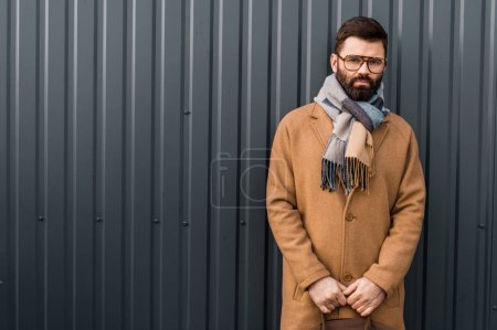 Photo for Handsome businessman standing in coat and scarf with textured wall on background - Royalty Free Image
