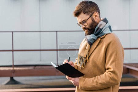 Focused businessman standing in coat and writing in notebook