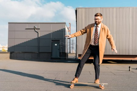 cheerful businessman in suit and coat riding on penny board